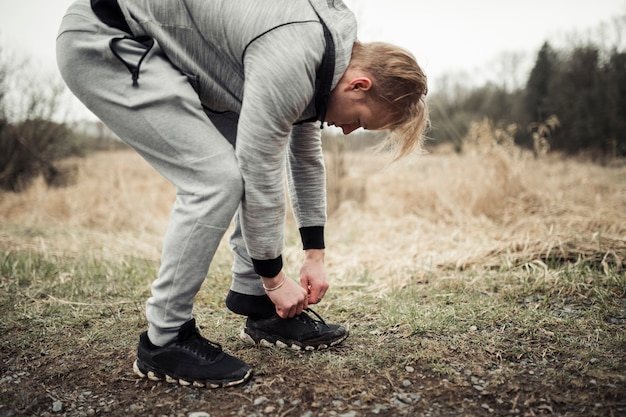 Young male jogger putting his sport shoes