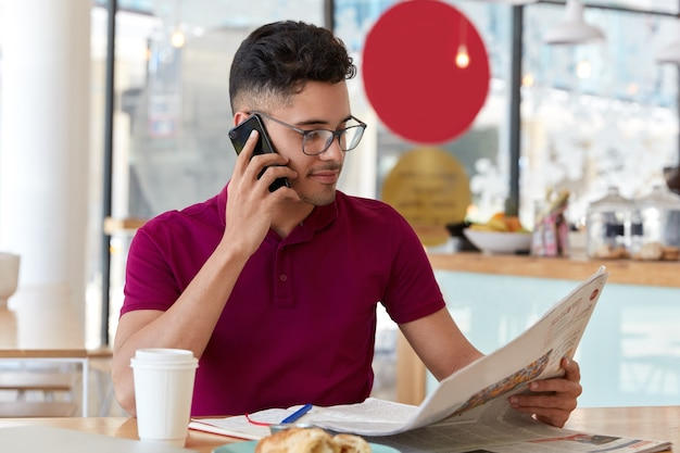 Young male journalist makes research in press, reads newspaper publication, holds cell phone, makes call, enjoys takeaway coffee, sits against cafe interior. people, leisure, mass media, technology