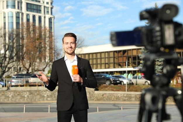 Молодой журналист-мужчина с микрофоном, работает на городской улице
