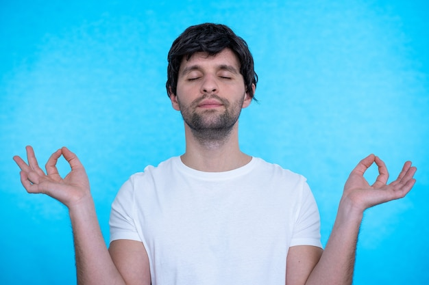Молодой мужчина держит глаза закрытыми во время практики йоги в помещении, медитирует, держась за руки в жесте мудры