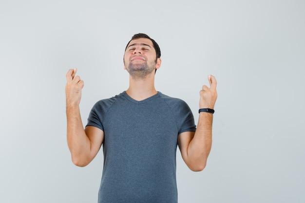 Молодой мужчина в серой футболке скрещивает пальцы и выглядит мирно