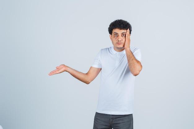 若い男性は頬に手を保ち、白いtシャツ、ズボンで何かを見せて、困惑しているように見えます。正面図。