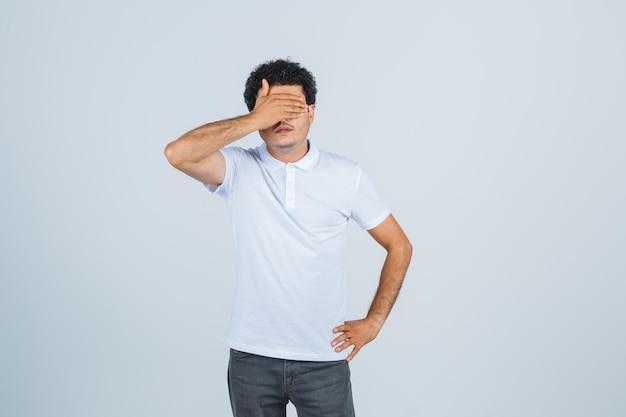 흰색 티셔츠, 바지를 입고 침착한 표정을 하고 있는 젊은 남성. 전면보기.