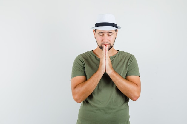 緑のtシャツと帽子で祈りのジェスチャーで手を保ち、希望に満ちた若い男性