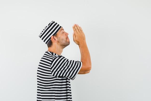 Молодой мужчина держит руки в молитвенном жесте в полосатой футболке и смотрит с надеждой