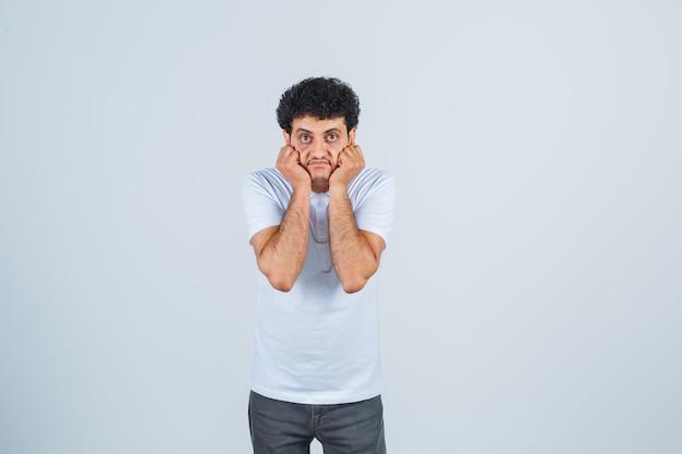 白いtシャツ、ズボン、不安そうな顔で頬に手を当てている若い男性。正面図。