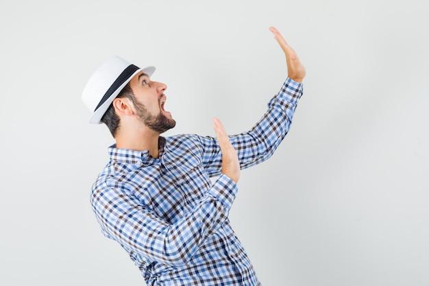Giovane maschio mantenendo le mani in modo preventivo in camicia a quadri, cappello e guardando spaventato. vista frontale.