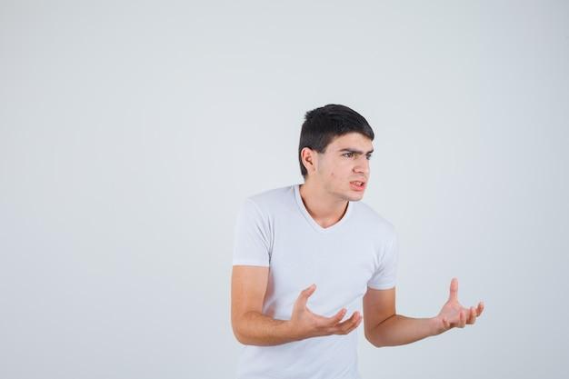 젊은 남성 티셔츠에 뭔가 잡으려고 손을 유지하고 심각한 찾고. 전면보기.