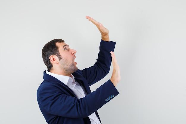 Молодой мужчина держит руки, чтобы защитить себя в рубашке и куртке и выглядит испуганным