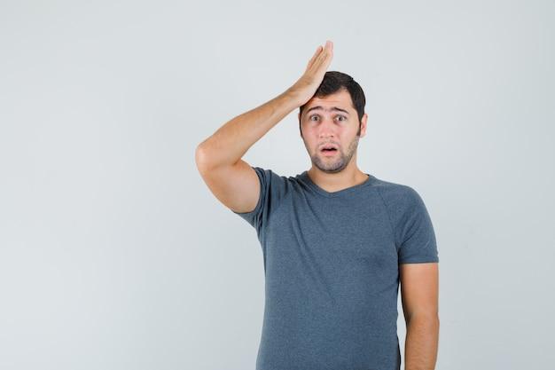 젊은 남성 유지 회색 티셔츠에 머리에 손을 들고 곰 곰을 찾고