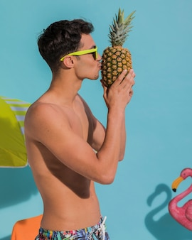 Young male kissing pineapple