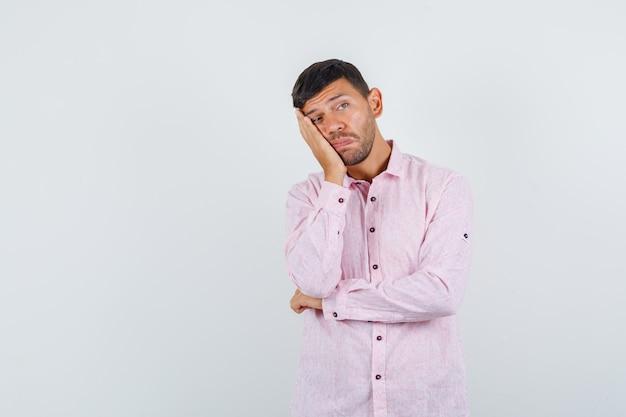 Молодой самец в розовой рубашке, прислонившись щекой к поднятой ладони и глядя задумчиво. передний план.