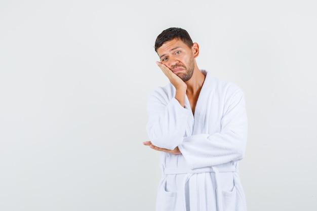 白いバスローブを着て上げられた手のひらに頬を傾けて動揺している若い男性。正面図。