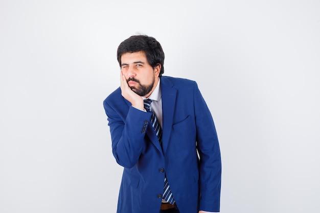 Giovane maschio appoggiato alla sua mano in camicia, giacca, cravatta e guardando concentrato, vista frontale.