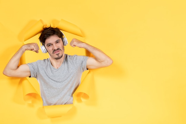 Young male listening to music in headphones and flexing yellow paper background ultrasound audio