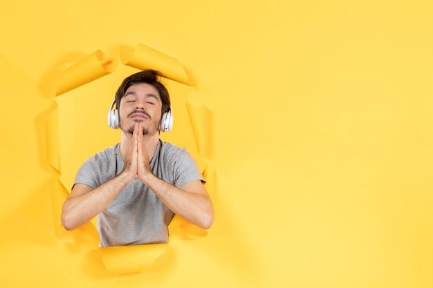 노란색 배경 오디오 초음파 소리에 헤드폰으로 음악을 듣는 젊은 남성