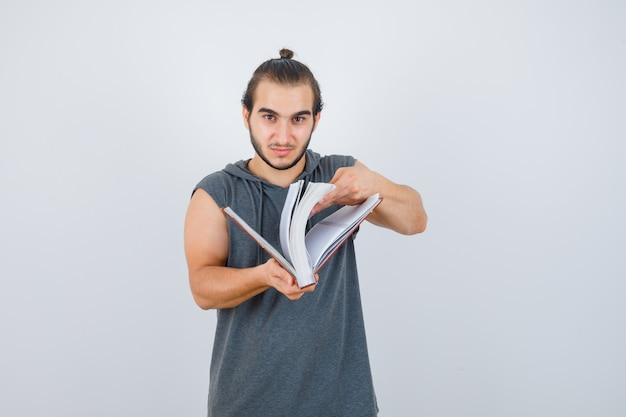 Giovane maschio guarda attraverso il libro in felpa con cappuccio senza maniche e sembra fiducioso. vista frontale.