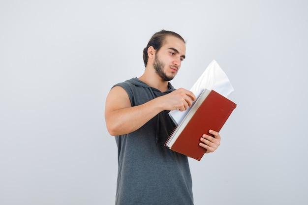 ノースリーブのパーカーでファイルを見て、集中して探している若い男性。正面図。