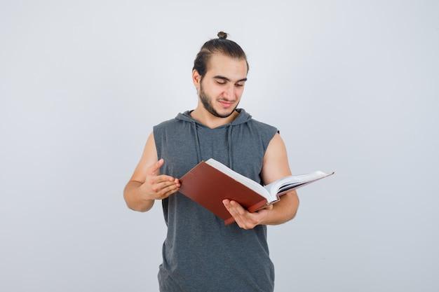 ノースリーブのパーカーで本を見て、集中して探している若い男性。正面図。