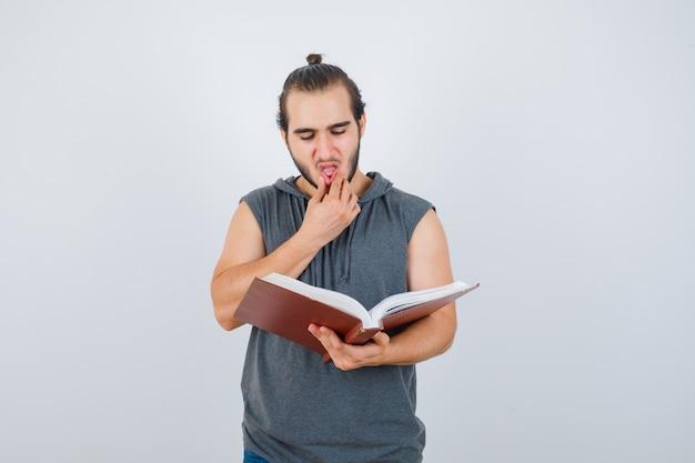 Молодой мужчина смотрит на книгу, держа руку за рот в толстовке без рукавов и смотрит вдумчиво, вид спереди.