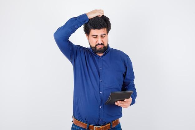 ロイヤルブルーのシャツの正面図で頭を掻きながら電卓を見ている若い男性。
