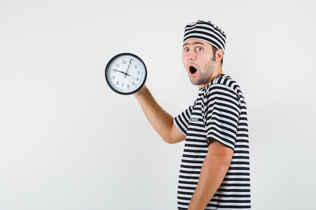 縞模様のtシャツ、キャップで時計を見て、驚いて見える若い男性。 。