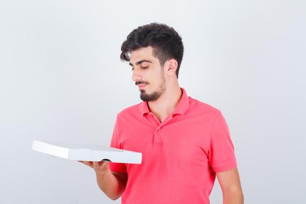T- 셔츠에 닫힌 된 피자 상자를보고 하 고 쾌활 한 찾고 젊은 남성. 전면보기.