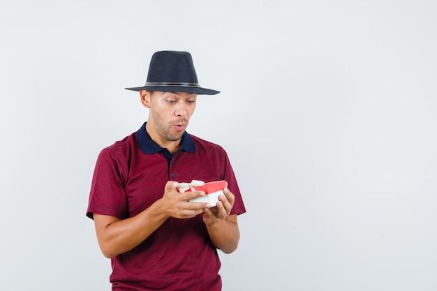 赤いシャツを着て贈り物を見て、驚いたように見える若い男性、正面図。テキスト用のスペース
