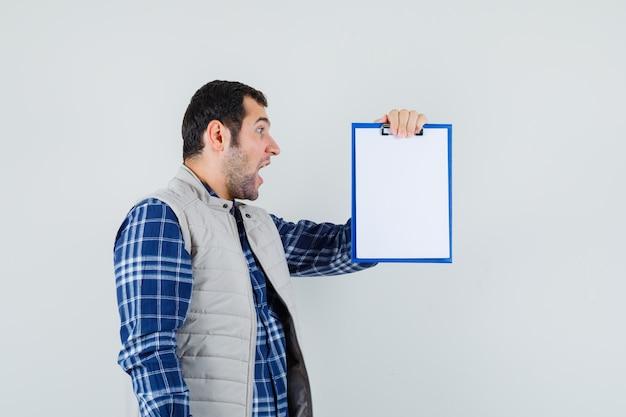 シャツ、ジャケットでクリップボードを見て、問題を抱えているように見える若い男性、正面図。