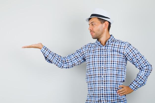 Молодой мужчина смотрит на его раздвинутую ладонь в клетчатой рубашке