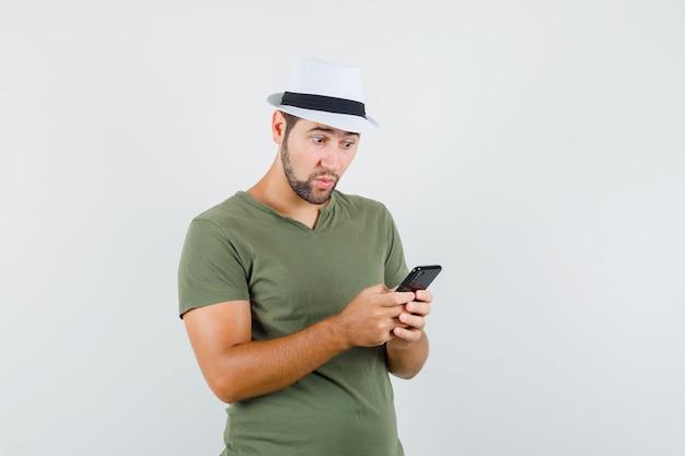 緑のtシャツと帽子で携帯電話を見て驚いて見える若い男性