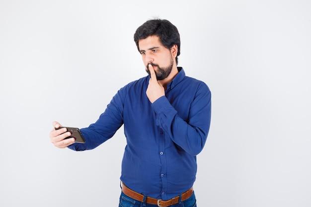 ロイヤルブルーのシャツの正面図で考えながら携帯電話を見ている若い男性。