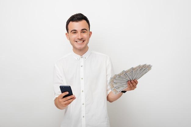 Молодой мужчина смотрит в камеру и держит его телефон и кучу денег.