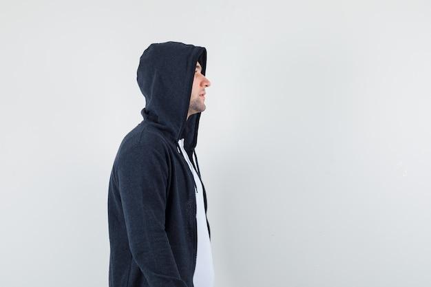 젊은 남성 티셔츠, 재킷에 그의 앞을보고 집중 찾고.