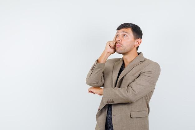 Giovane maschio che guarda lontano in giacca marrone grigiastro e sembra pensieroso. vista frontale. spazio libero per il tuo testo