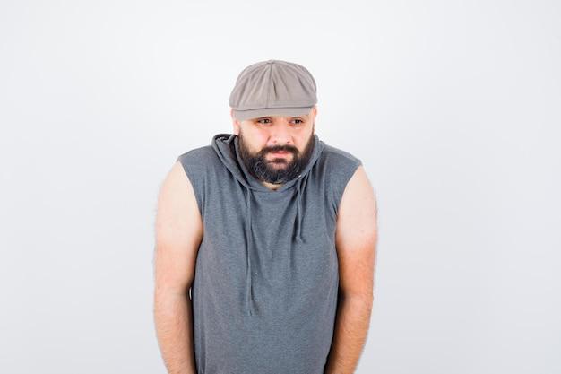 Молодой мужчина смотрит в сторону в толстовке без рукавов, кепке и скучает, вид спереди.