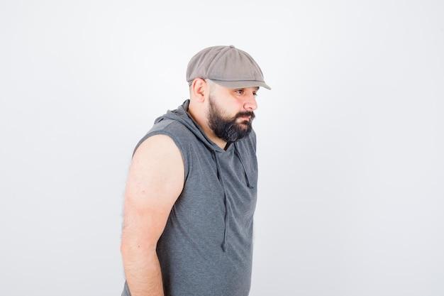 Молодой мужчина смотрит в сторону в толстовке без рукавов, кепке и выглядит уверенно, вид спереди.