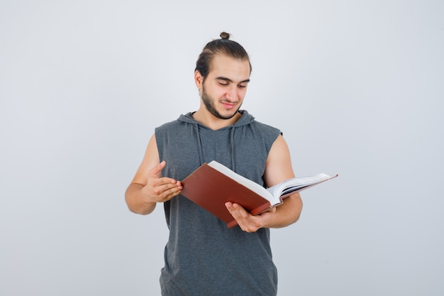 Young male looking at book in sleeveless hoodie and looking focused. front view.
