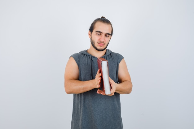 Young male looking at book in sleeveless hoodie and looking thoughtful. front view.