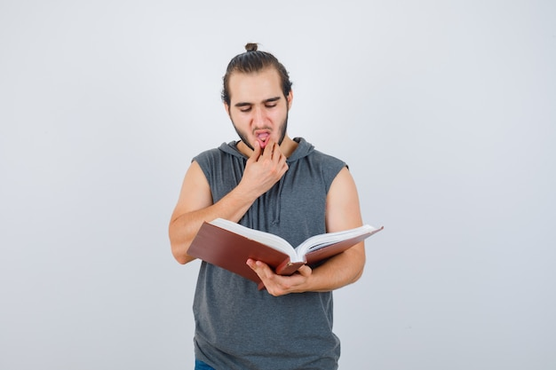 Young male looking at book while holding hand on mouth in sleeveless hoodie and looking thoughtful , front view.