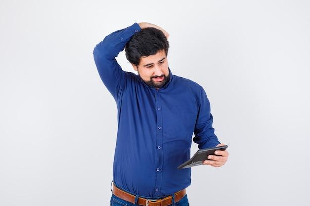 Giovane maschio che esamina calcolatrice mentre tiene la mano sulla testa nella vista frontale della camicia blu reale.