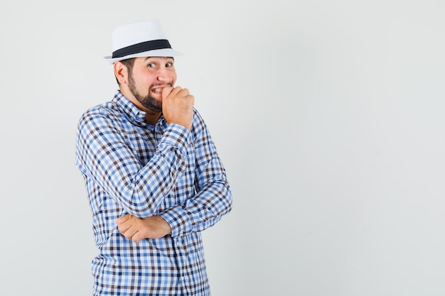 Giovane maschio che guarda l'obbiettivo in camicia controllata, cappello e guardando imbarazzato, vista frontale.