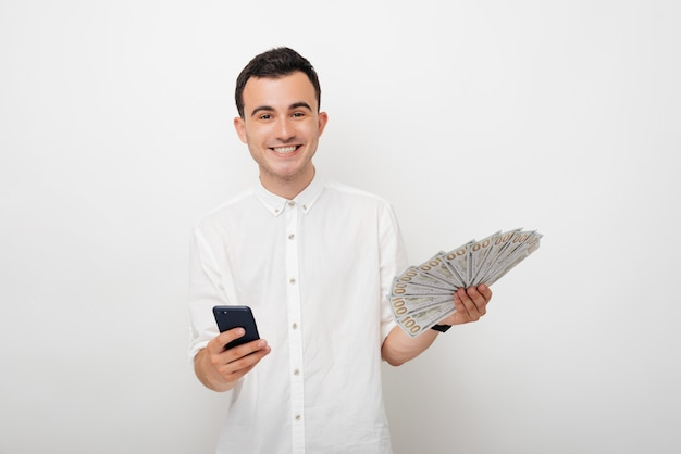 Young male looking at the camera and holding his phone and a bunch of money .