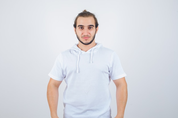 Young male looking at camera in t-shirt hoodie and looking confident , front view. Free Photo