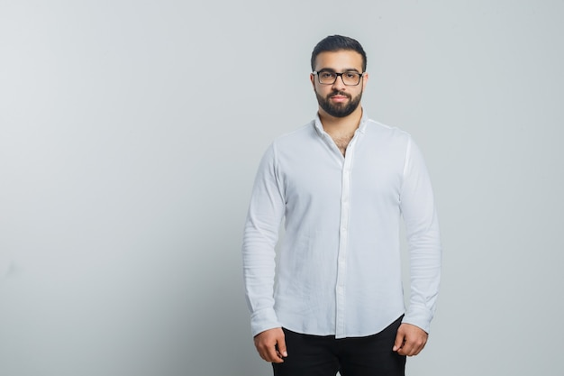 Young male looking at camera in white shirt, pants and looking handsome