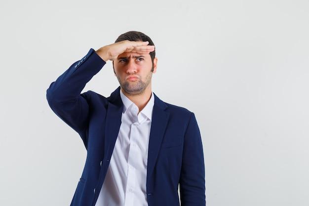Giovane maschio che guarda lontano con la mano sopra la testa in camicia, giacca e guardando pensieroso
