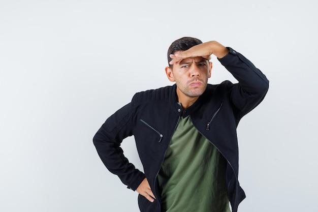 Молодой мужчина смотрит вдаль с рукой над головой в футболке, куртке и задумчиво, вид спереди.