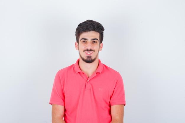 Молодой мужчина смотрит в розовую футболку и выглядит веселым, вид спереди.