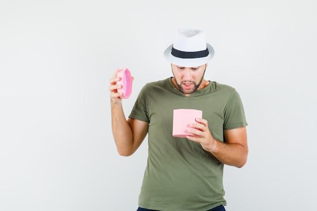 Giovane maschio che esamina il contenitore di regalo in maglietta e cappello verdi, jeans e che osserva stupito