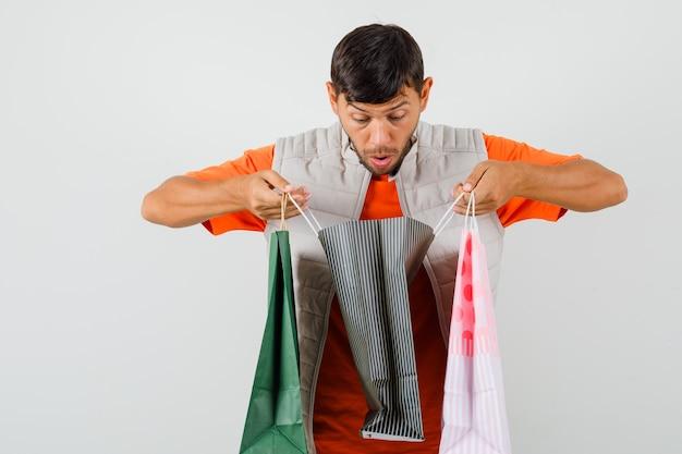 Tシャツ、ジャケットの買い物袋を見て、驚いて見える若い男性。正面図。